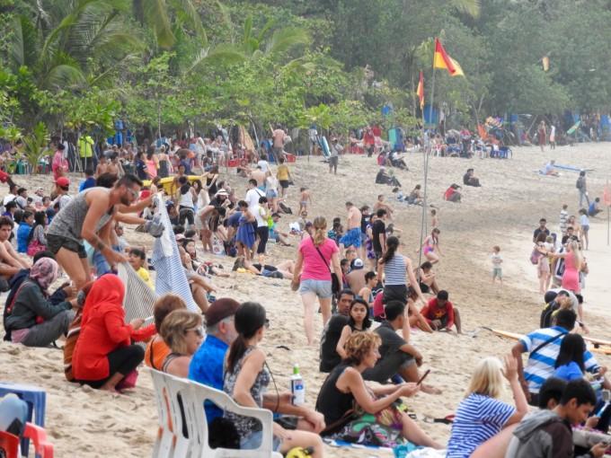 クタビーチに座る多くの人