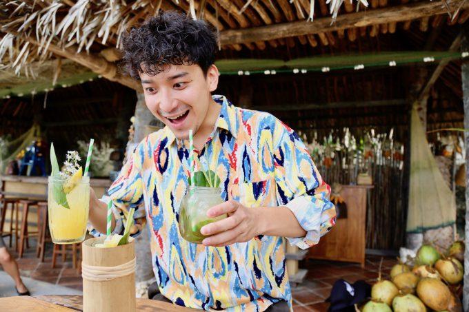 バリ島アヤナのクブビーチクラブのカクテルを持つカイリ