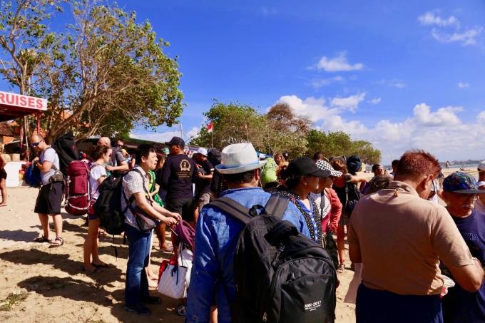 レンボンガン島へ行くために大きな荷物を持つ人々